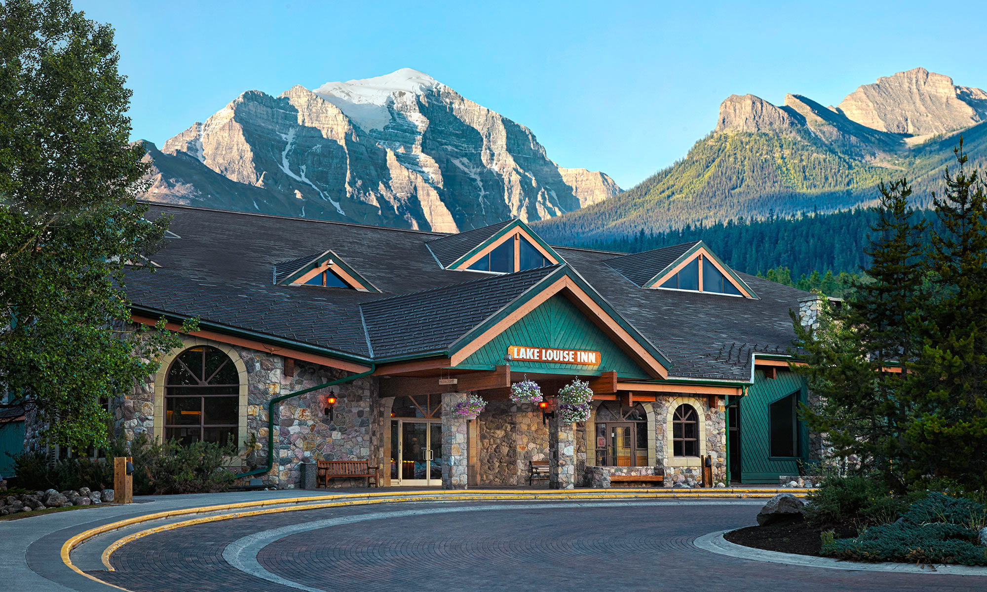 Late afternoon Lake Louise Inn entrance with end of day light on large rocky mountains behind