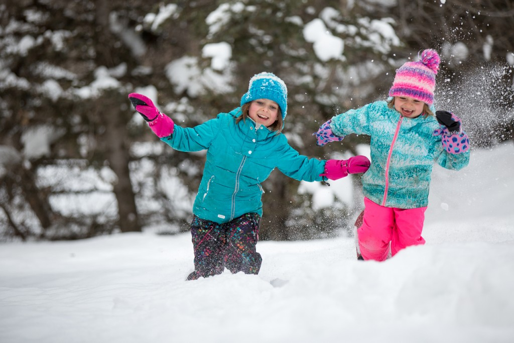two young girls playing in the deep snow laughing and smiling