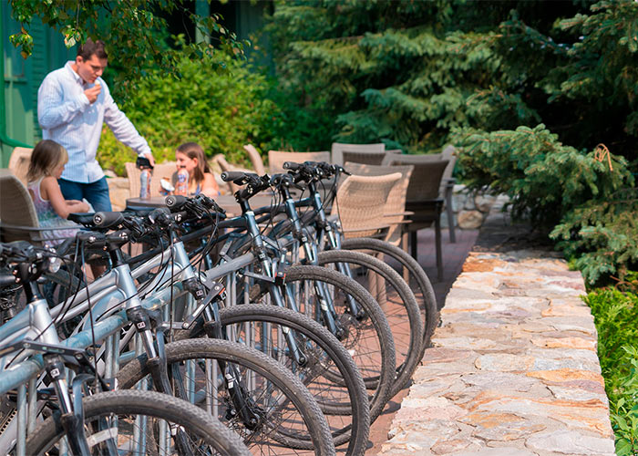 Complimentary bike rentals lined up outside the resort with father and daughters sitting at table nearby