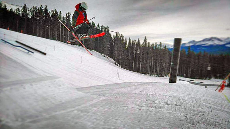 Skier in terrain park getting air over jump