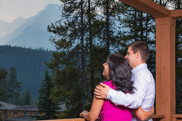 Couple enjoying the view from the balcony surrounded by pine trees and mountain views