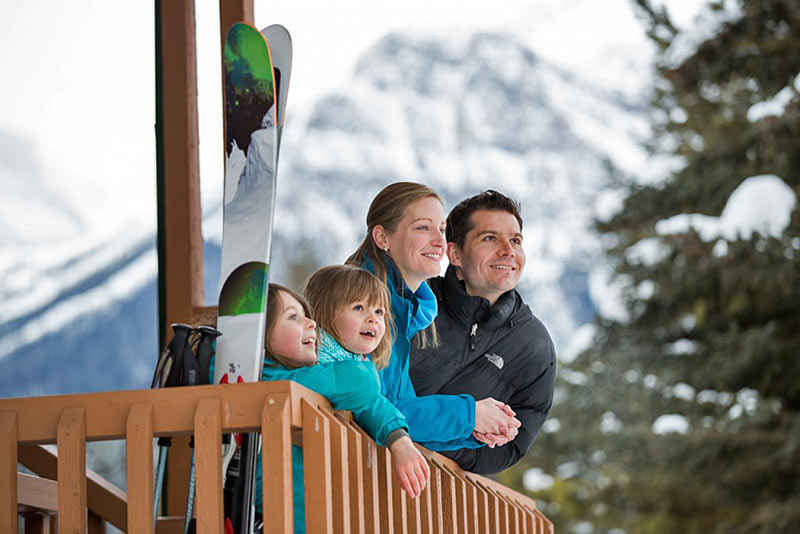 Family in winter gear with skis looking out from balcony with snow mountains in background