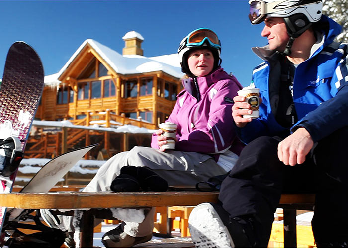 Snowboarders sipping hot chocolate on blue bird day outside ski lodge at Lake Louise Ski Resort