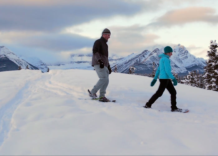 Couple on top of mountain snowshoeing