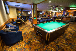Pool table and sitting area next to bar and large tv screens at Explorers Lounge