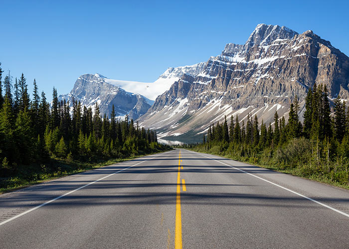 Road to Lake Louise surrounded by forest and mountain peaks