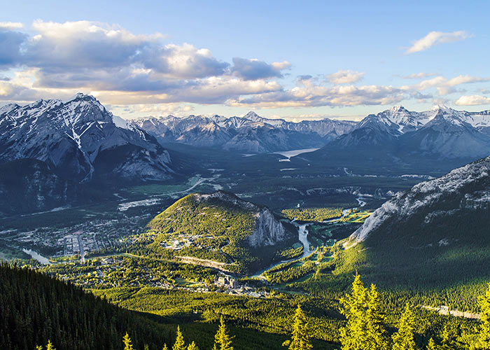The setting Sun casting golden rays on the town of Banff in Alberta, Canada, taken from Sulphur Mountain