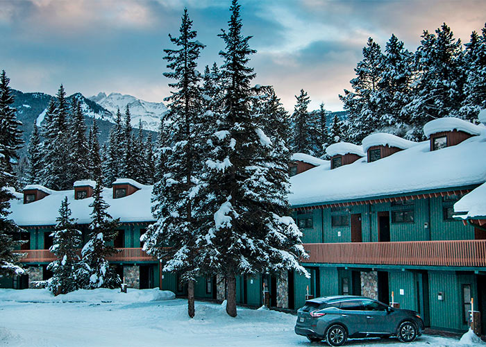 Exterior of one of the lodgings at the Lake Louise Inn, car parked next to room
