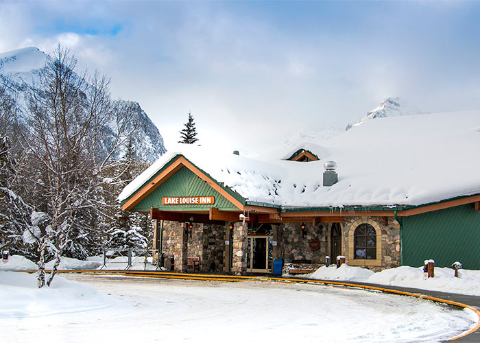 Snow covered entrance of the Lake Louise Inn surrounded my mountains