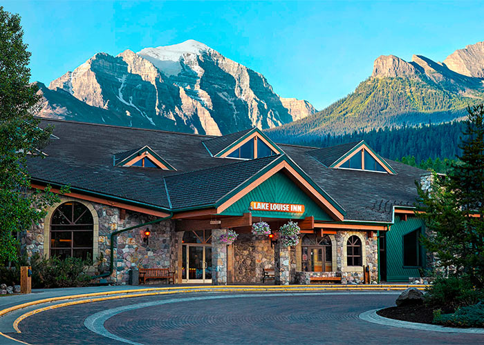 Exterior of reception building at the Lake Louise Inn surrounded by mountains