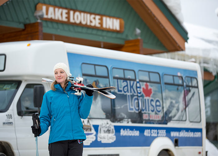 skier carrying skis from ski shuttle bus in front of Lake Louise Inn