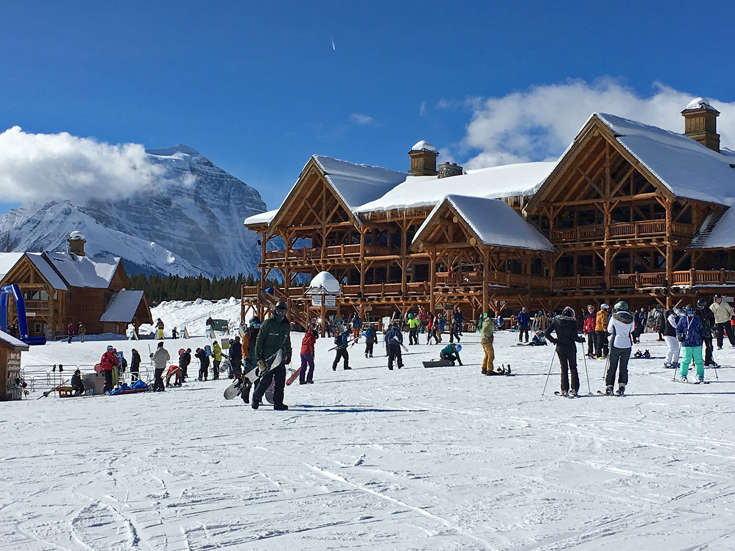Lake Louise Ski Resort Lodge in winter with lots of skiers and boarders getting ready to go up lift