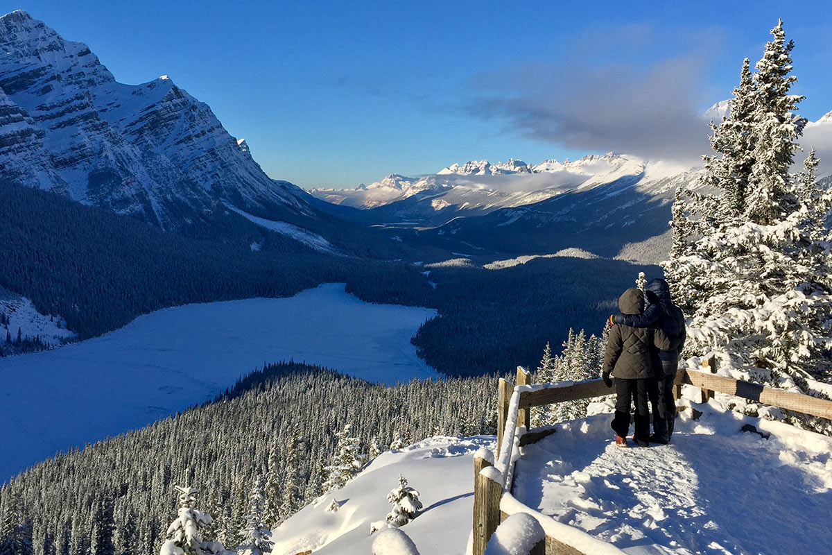Couple embracing on overlook of Peyto Lake on blue sky winter day