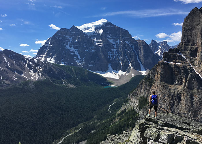 Hiker looking over view of Mount Temple from large rock