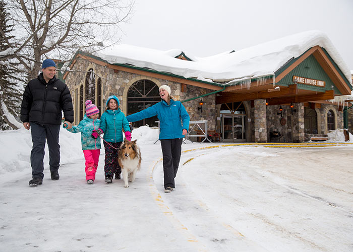 Happy family walking dog at Lake Louise Inn