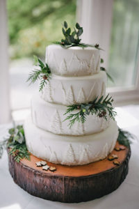 layered wedding cake decorated with forest images and natural accents