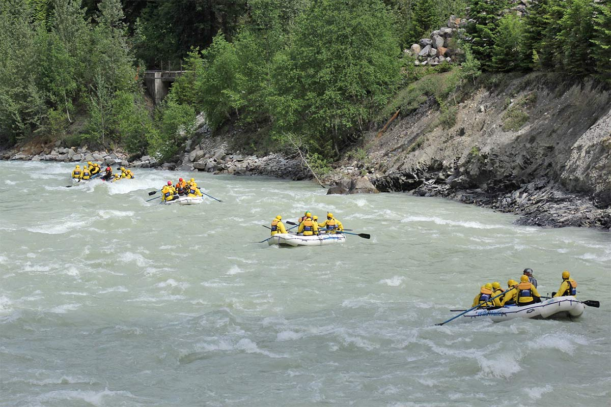 4 full rafts of people enjoying a ride down the Kicking Horse River