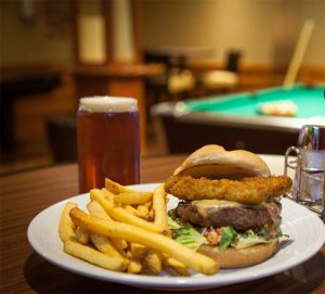 specialty burger with fries and a pint with a pool table in background