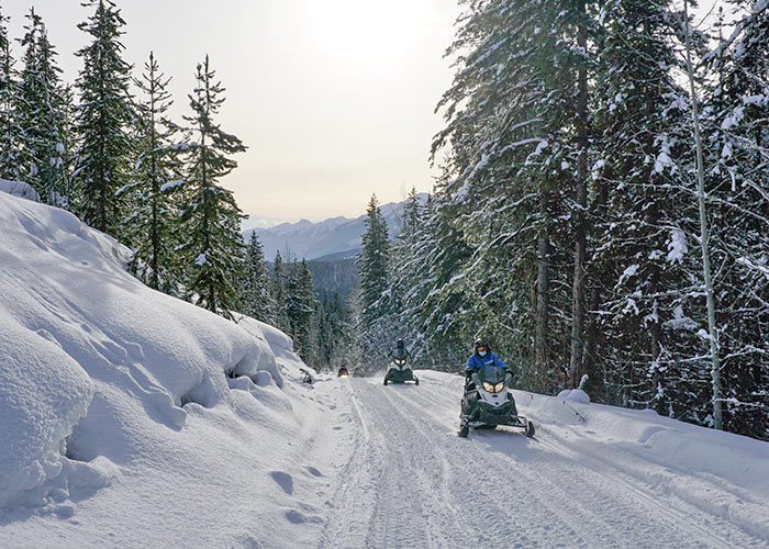 Snow mobiling on snowy road through forest with mountains views